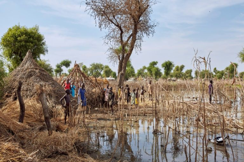 Figure 5 - Children stand among the rooftops of homes after the Yusuf Batir refugee camp in South Sudan was hit by flooding. Source: AFP Photo/Alex McBride, (2019)